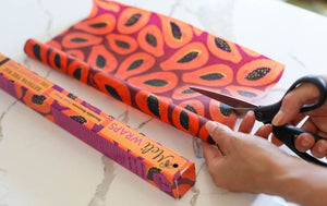 Meli Wraps® Beeswax Wrap Bulk Roll in Purple Papay Print pictured next to its colorful box. A pair of hands holds a pair of scissors showing how you can easily cut these bulk beeswax food wraps to any size you need!