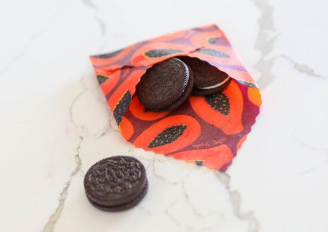 Meli Wraps Beeswax Wraps photo of a bulk roll of beeswax wraps in purple papaya print folded into an envelope to hold oreo cookies.