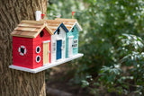 Birds nesting box in the form of 3 beach huts joined togethe in predominantly red, white and turquoise