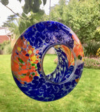 Blue hanging glass bird feeder - Circular glass ring in predominantly blue with orange and white, hanging on a tree in a garden.
