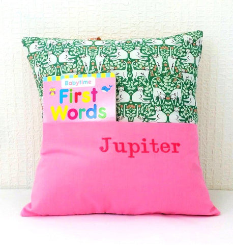 Pink and green patterned cushion with cat design and children's reading book tucked into cover