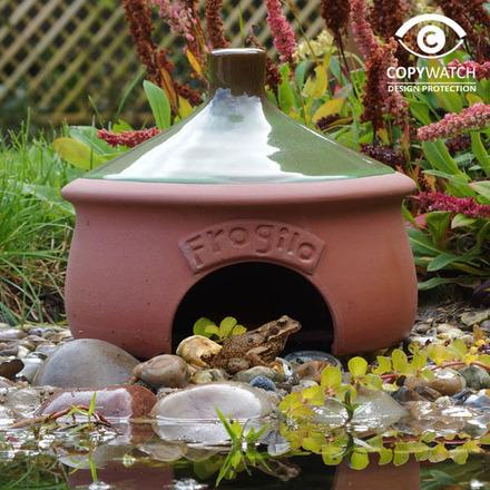 Round earthenware frog house with small arched doorway and green domed roof