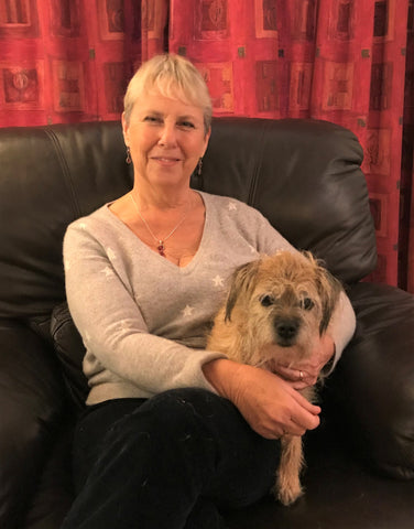 Kate Findlay and Jess the Border Terrier sitting on a brown leather chair in front of red curtains