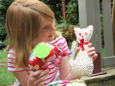 Little girl playing indoors with hand sewn soft toys