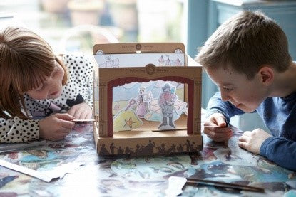 A girl and a boy working together to make a theatre in a box on a table top