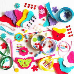 Brightly coloured contents of jewellery design kit including felt cut outs and beads