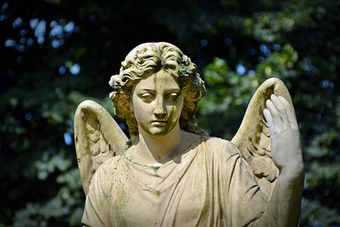Stone statue of Victorian death angel as an elaborate graveside decoration