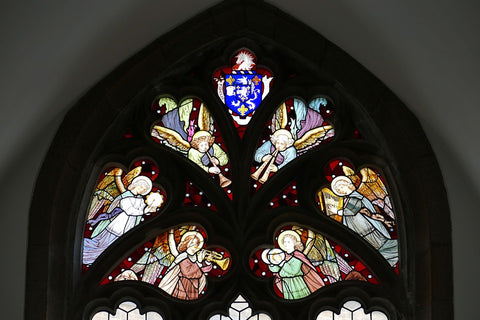 Medieval stained glass window in church showing angels celebrating and worshipping God