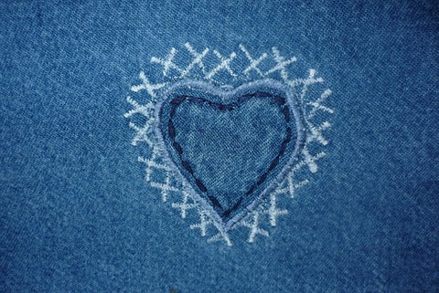 Heart shaped symbol on denim surrounded by white cross-stitch kisses