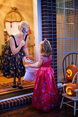 Girl trick or treating at house with lady holding feathered mask over her face