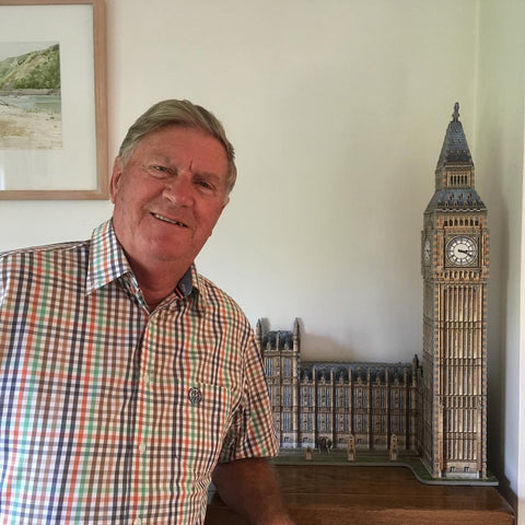 Man standing in front of completed Wrebbit Big Ben 3D jigsaw puzzle