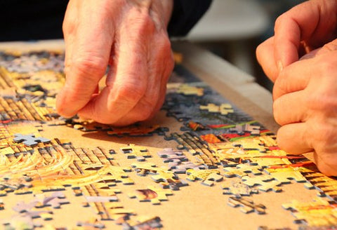Two people (only hands seen) piecing together jigsaw puzzle