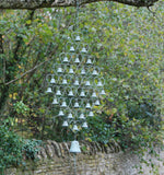 Tiny bells hang inside a metal frame that is diamond shaped with a larger bell hanging from the bottom, in a garden.