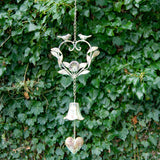 Metal wind chime in the shape of a heart, decorated with birds and a rose, a bell hanging below on a chain, in the garden against a background of leaves.