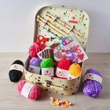 Open craft kit suitcase with contents visible - 7 different shades of wool, knitting needles, scissors, a booklet with BUMPER Knitting & crochet kit instructions.