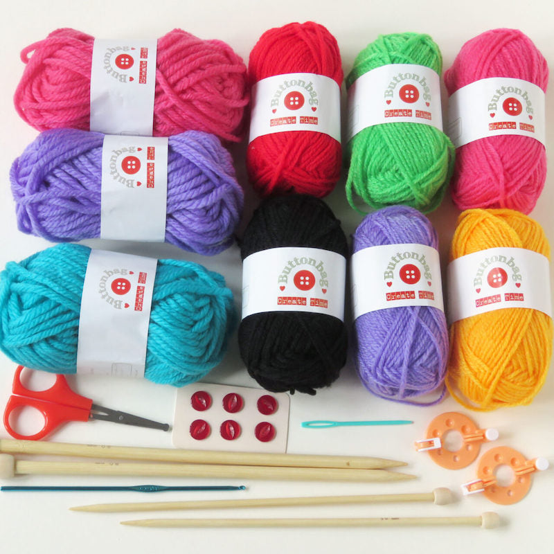 Contents of the Bumper Knitting and crocket kit - 9 balls of wool in different colours with Buttonbag on the labels, buttons, pompom making circles, two pairs of needles of different diameters, wool needle, crochet hooks scissors