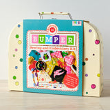 Large buttonbag Cream suitcase decorated with buttons with blue wrap around sleeve with the words BUMPER Sewing and Embroidery Kit, a buttonbag craft kit, everything you need to learn how to sew and embroider, age 8+, beginner friendly