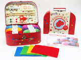 Buttonbag knitting kit - red suitcase open showing packed contents, closed suitcase with wrapper showing its a knitting kit, button bag instruction leaflet, 4 pieces of coloured felt