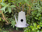 White enamelled bird nest box in the shape of a tall French style teapot hanging in a garden