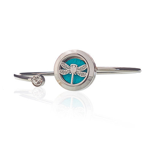 Stainless steel cuff type bracelet with a locket bearing the image of a dragonfly with a turquoise essential oil pad behind it.