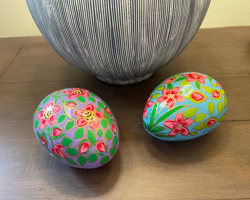 Two paper mâché egg shaped boxes, one with a mauve background, one in turquoise, decorated similarly with pink/red flowers and green leaves. Displayed on a table by a lamp.