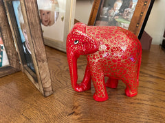 Elephant ornament in red with gold decorations alongside photo albums