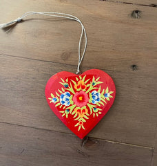 Red heart decorated with flowers displayed on a wooden table