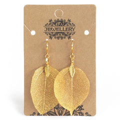 Gold coloured earrings made from natural leaves on a simple card