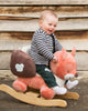 Child sitting on an Oscar the Fox Nattou rocker - Peach Perfect