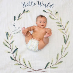 Happy baby holding toes on the Hello World baby blanket with a 'I am 7 months old' card