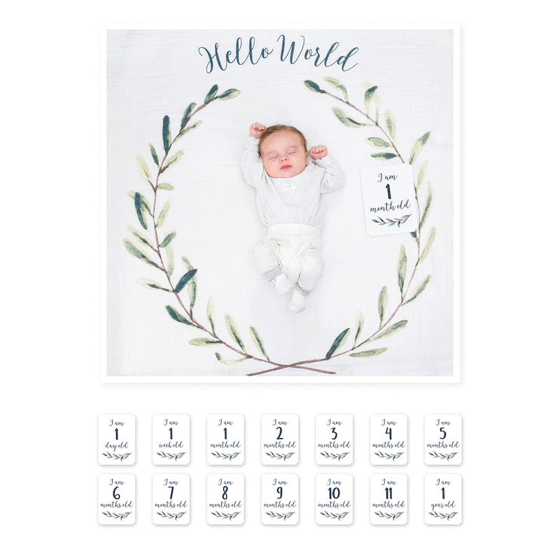 Sleeping baby in the middle of a circular leaf and twig design on a cream background with Hello World printed at the top of the swaddle cloth and a 'I am 1 month old' milestone card