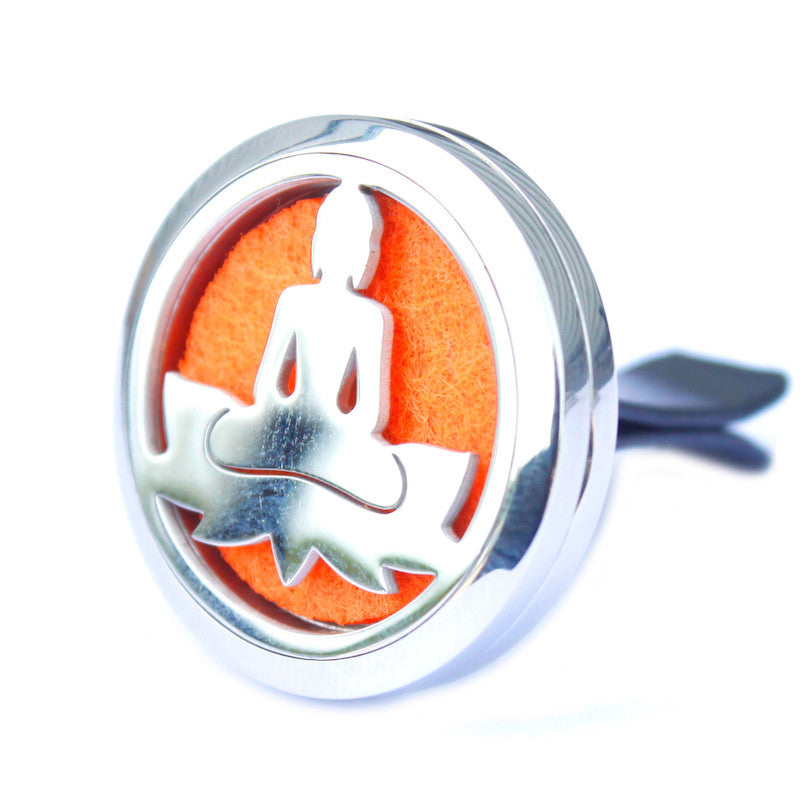 Aromatherapy diffuser for the car in silver metal with a cut out image of buddah sitting on a lotus flower. Inside the locket is an orange felt pad for th essential oil