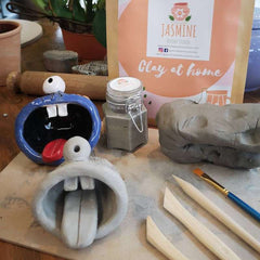 Two clay 'monsters' - wide mouths with tongue sticking out and a single eye on top. One left natural, the other painted blue with black interior and white teeth and eyes. Surrounded by the Clay Kit contents