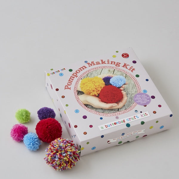 Pompom making kit box with picture of pompoms in different sizes and colours, a button bag craft kit, 6+ beginner friendly plus some made up pompoms.