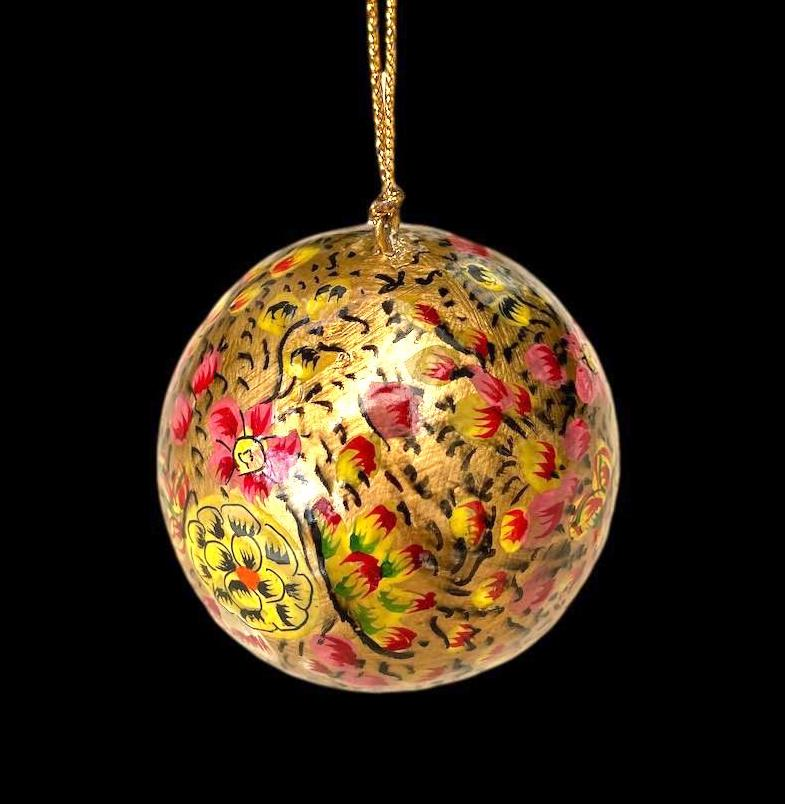 Gold ornamental ball with small red/pink flowers and a larger yellow and black flower