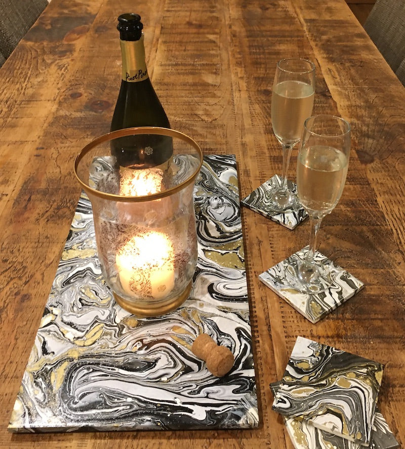 White, black and gold table protector with coasters with candle and bottle of fizz - Peach Perfect