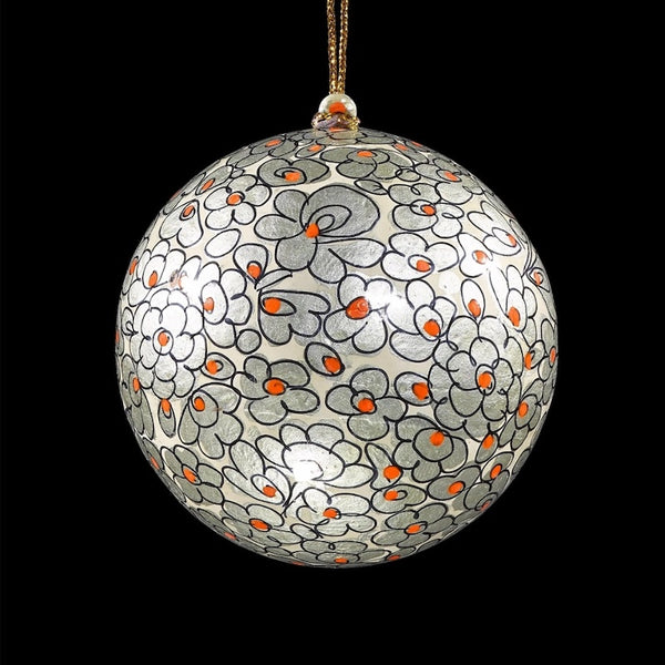 An ornamental silver bauble decorated with simple flowers in a darker silver with centres in bright orange.