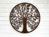 Rusty brown metallic tree shape with birds in the branches set inside a metal circle, hung against a white painted brick wall