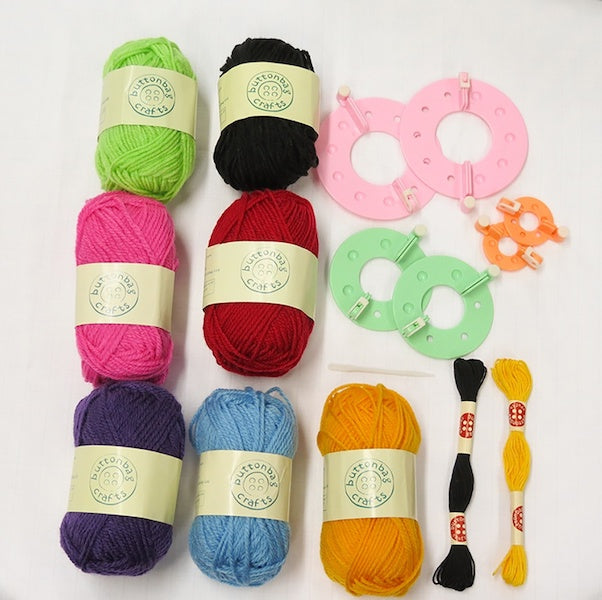 Contents of Pompom making kit - 7 balls of wool in different colours, pompom hoops in 3 sizes, 2 embroidery thread skeins in yellow and black