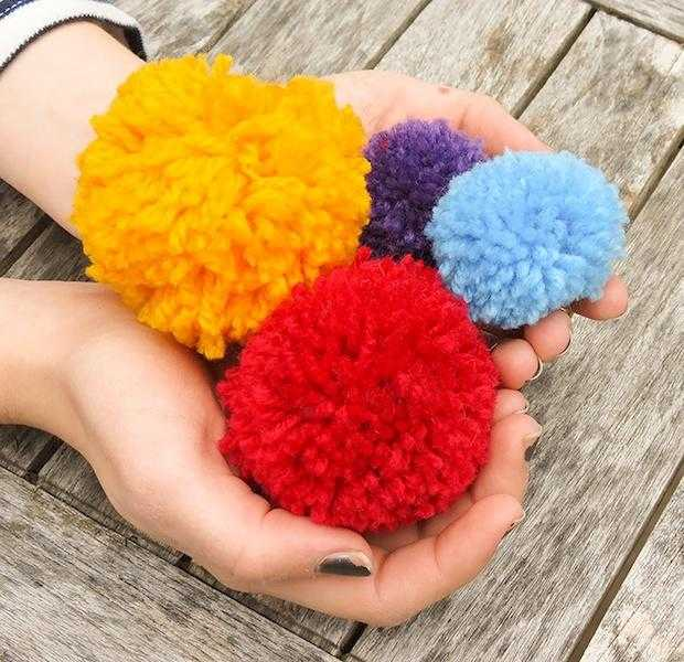 Fluffy pompoms held in cupped hands