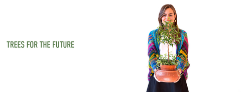 A friendly smiling girl wearing a colorful handknit sweater holding out a baby tree for you to see. The text next to this photo reads 'Trees for the Future'.
