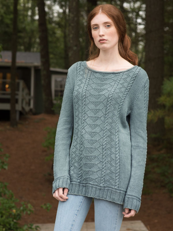 The Carra knit summer sweater on a young lady standing in the woods.