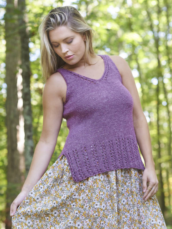The Eleri summer sleeveless top on a young lady standing in the woods, knit in the colorway Heather 7937.