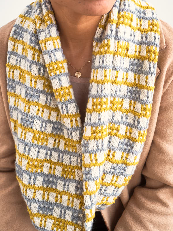 Kasiani, a modern eye-catching knit cowl shown in the colors #5801 Pearl, #5811 Golden, and #5806 Silver.