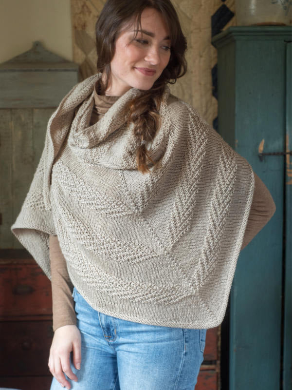 The Orford Shawl in a the color Oat 3305 on a smiling model