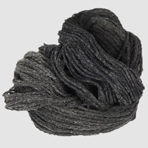 Color Charcoal. A dark grey kettle-dyed skein of Mountain Meadow Cheyenne Aran Yarn.