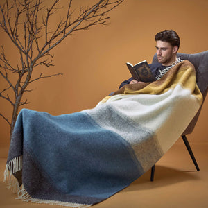 A man reading a book with a blue and grey striped Lopi Wool Blanket.