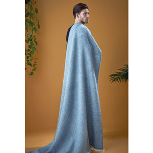 A man with a light blue woven Lopi Wool blanket drapped on his shoulder.