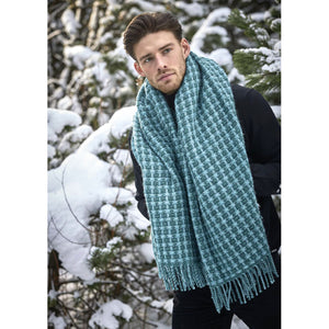 A man wearing a turquoise blue plaid Lopi wool blanket as a scarf in the snow.