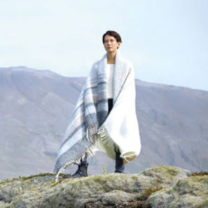 Lopi Wool Blankets 2020 offered by Paradise Fibers. A woman on Icelandic hillside wearing blanket.